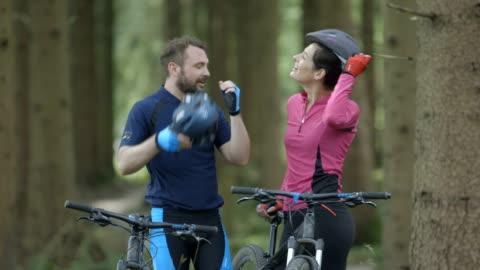 vídeos y material grabado en eventos de stock de couple cycling through forest track - casco herramientas profesionales