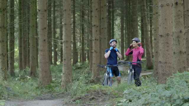 Couple cycling through forest track