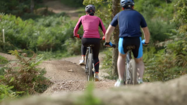 couple cycling through uneven forest track - uneven stock videos & royalty-free footage