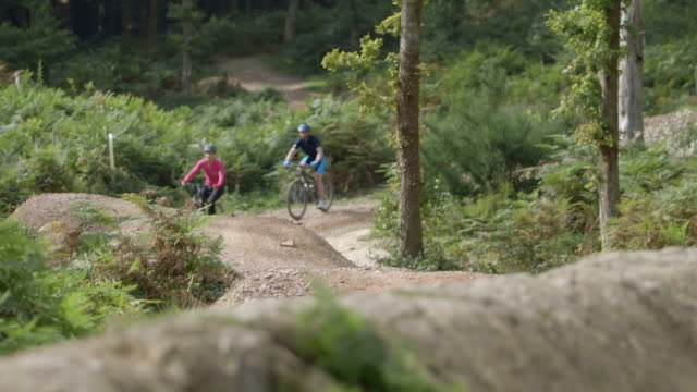 Couple cycling through uneven forest track