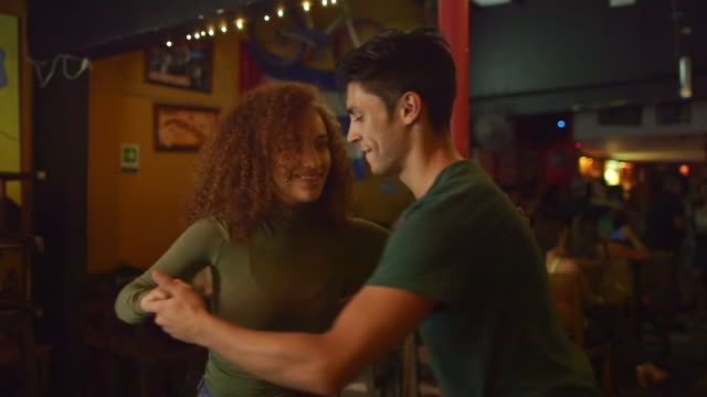 a couple dance together in a salsa club - サルサダンス点の映像素材/bロール