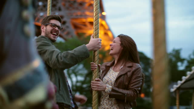 MEDIUM SHOT couple dances and laugh as they ride a carousel near the Eiffel Tower in Paris