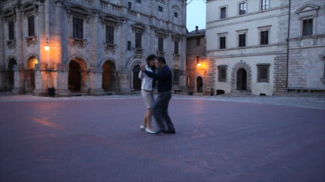 A couple dances at dusk in the town square of Montepulciano, Italy