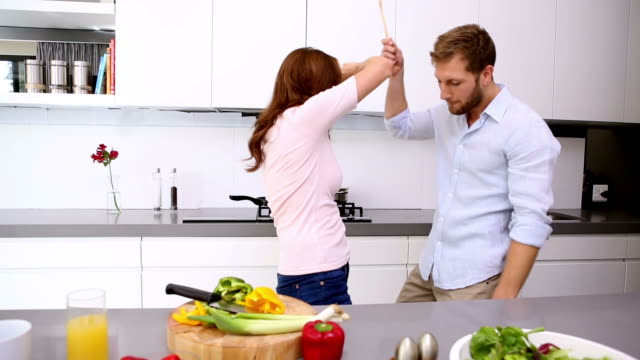 couple dancing and acting silly in the kitchen - cutting board stock videos and b-roll footage