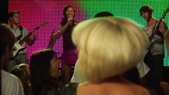 MS SLO MO Couple dancing and taking photograph at rock concert / London, UK