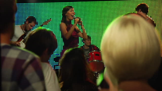 ms r/f slo mo couple dancing and taking photograph at rock concert / london, uk - 30 34 ��r bildbanksvideor och videomaterial från bakom kulisserna