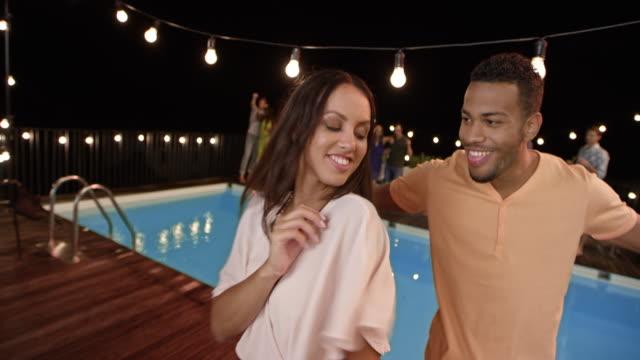 paare tanzen auf einer party am pool in der nacht zusammen mit ihren freunden - wickelkleid stock-videos und b-roll-filmmaterial