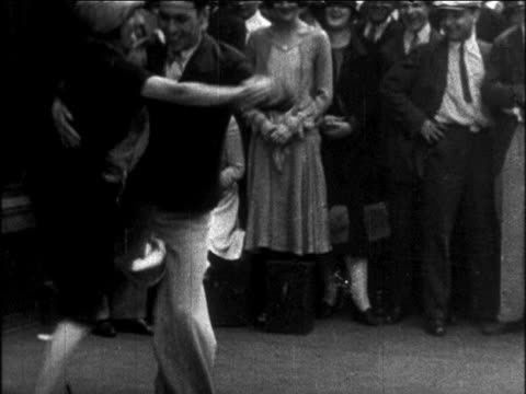 b/w 1926 couple dancing charleston outdoors on sidewalk as crowd watches / newsreel - 1926 stock videos & royalty-free footage