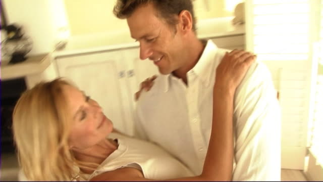 stockvideo's en b-roll-footage met couple dancing in kitchen - mid volwassen koppel