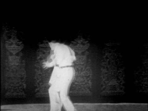 B/W 1925 couple dancing lindy hop on stage / man doing splits + somersault / Chicago / newsreel