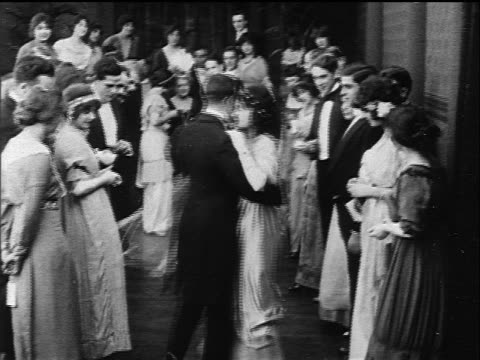 vidéos et rushes de b/w 1914 couple dancing past row of people at formal party / onlookers clap - tenue habillée