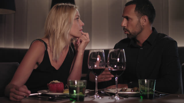 couple dating, talking, drinking, eating and flirting while having dinner and red wine in a hotel restaurant - blonde woman with long hair and tanned man with short dark hair and trimmed beard, both in their 30s. he wears a black shirt, she a black dress. - black dress stock videos & royalty-free footage