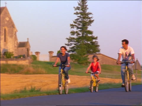 PAN couple + daughter riding bikes on country road / France