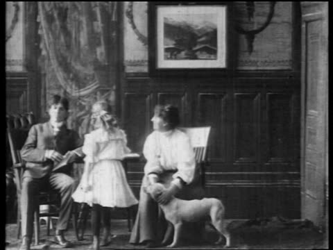 b/w 1906 couple + daughter sitting in living room petting dog / girl sits on father's lap - 1906 stock-videos und b-roll-filmmaterial