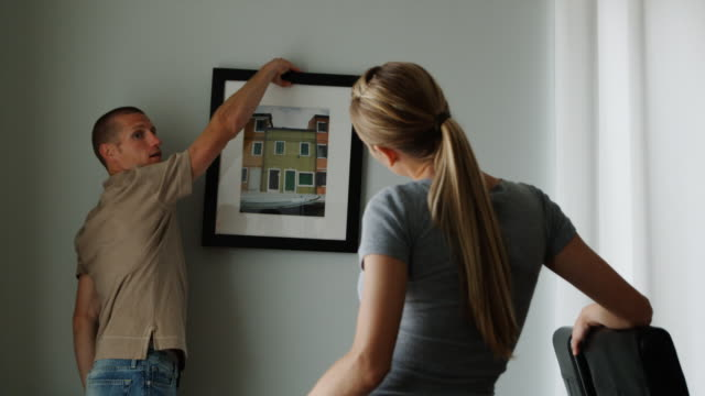 couple deciding which picture to hang on the wall - see other clips from this shoot 1418 stock videos & royalty-free footage