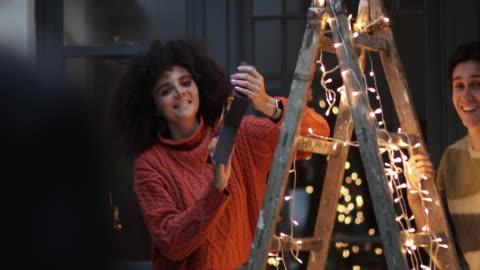 vídeos de stock e filmes b-roll de couple decorating an alternative christmas tree - fairy lights