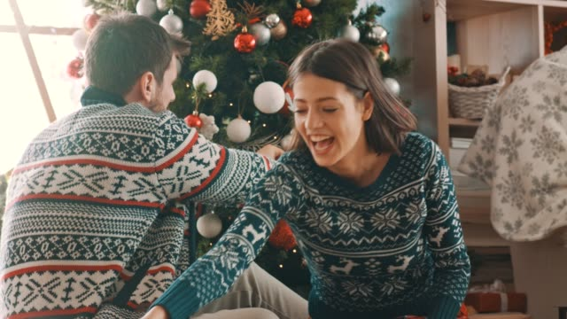 couple decorating christmas tree together - ornato video stock e b–roll