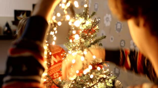 vídeos de stock e filmes b-roll de couple decorating christmas tree.christmas time is even more fun with you - abeto