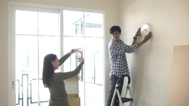 couple decorating clock at new home - changing clock stock videos and b-roll footage