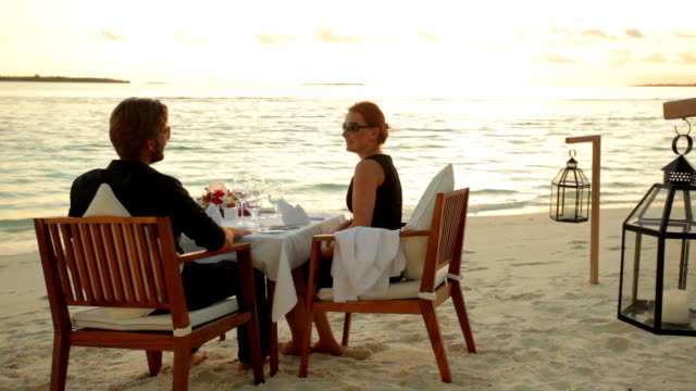vidéos et rushes de couple dining on beach at sunset - déjeuner