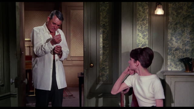 1963 couple (cary grant and audrey hepburn) discuss lying as grant changes his shirt - james coburn stock videos & royalty-free footage