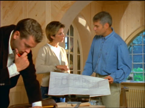 couple discussing blueprints in house under construction while male architect writes in foreground - femmina con gruppo di maschi video stock e b–roll