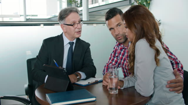 couple discussing investment plan with financial advisor - loan stock videos & royalty-free footage