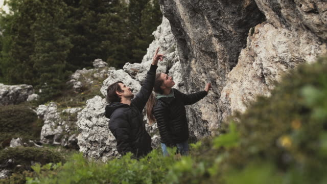 couple discussing while looking at rock structure - winter coat stock videos & royalty-free footage
