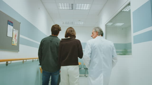 couple discussing with doctor in hospital corridor - corridor stock videos & royalty-free footage