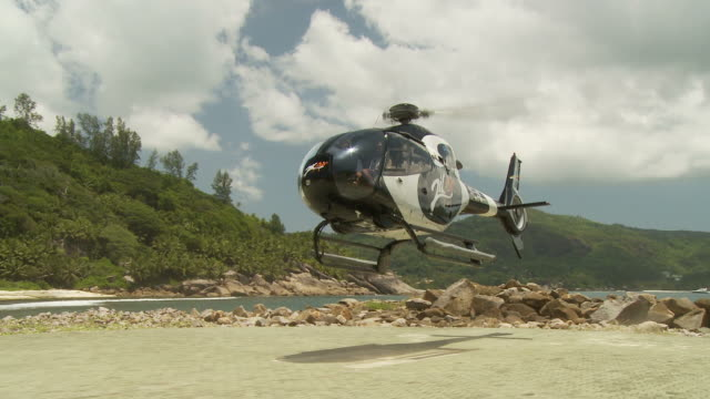 ms couple disembarking helicopter / seychelles - hubschrauber stock-videos und b-roll-filmmaterial