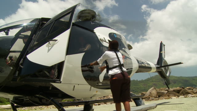 ws la couple disembarking helicopter / seychelles - male with group of females stock videos & royalty-free footage