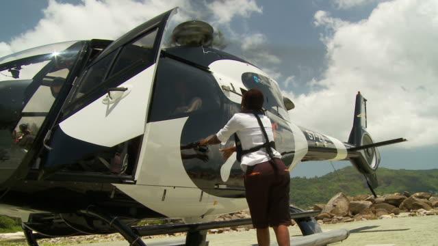 stockvideo's en b-roll-footage met ws la couple disembarking helicopter / seychelles - man met een groep vrouwen