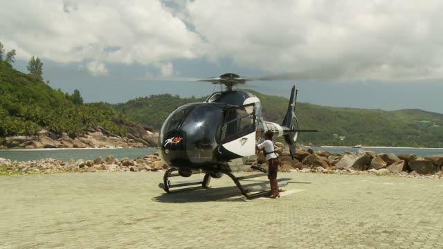 ws couple disembarking helicopter / seychelles - 男性と複数の女性点の映像素材/bロール
