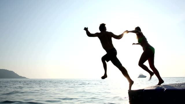 Couple dive into sea from pier, sunrise