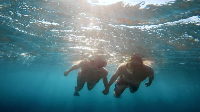 POV Couple diving holding hands