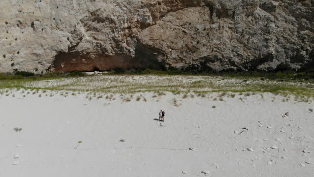 vídeos de stock e filmes b-roll de couple doing a boomerang drone selfie in the idyllic beach of the shipwreck in greece. - bumerangue