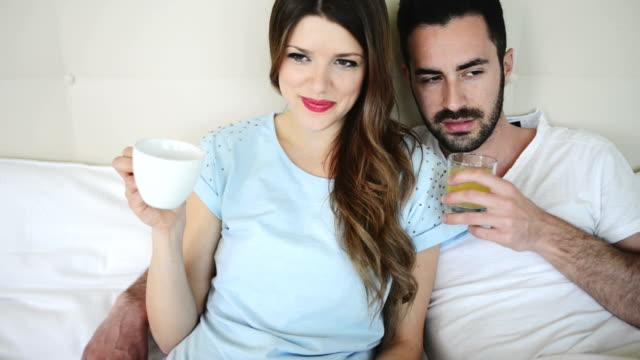 vídeos de stock e filmes b-roll de casal dando o pequeno-almoço na cama do quarto de hotel - casado