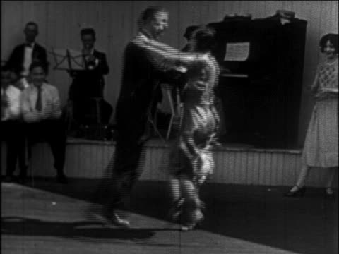 b/w 1926 couple doing charleston on outdoor dance floor / musicians in background / newsreel - 1926 stock videos & royalty-free footage