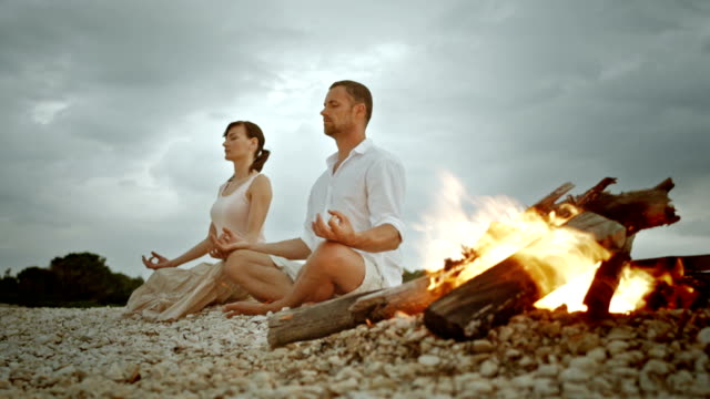 pan couple doing half lotus on beach by the fire - serene people stock videos & royalty-free footage