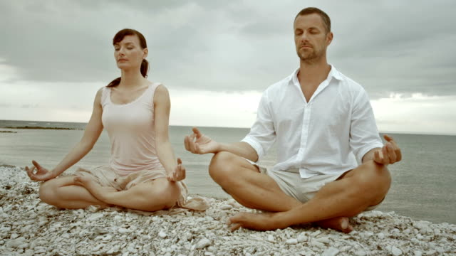TU Couple doing half lotus yoga pose by the sea