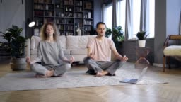 Couple doing morning exercise in home interior
