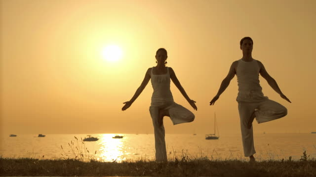 HD: Couple Doing Relaxation Exercises By The Sea