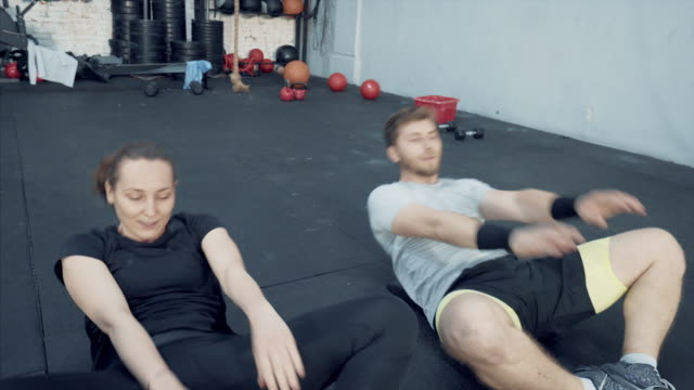 Couple doing sit-ups in the gym.