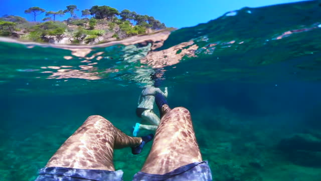 couple doing snorkel exploring the medes islands in the shoreline of costa brava mediterranean sea during summer vacations in a paradise place recorded with dome and underwater view. - 30 34 jahre stock-videos und b-roll-filmmaterial