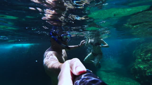 Couple doing snorkel recording themselves exploring the natural cave in the shoreline of Costa Brava Mediterranean Sea during summer vacations in a paradise place recorded with dome and underwater view.