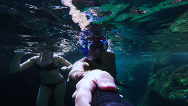 couple doing snorkel recording themselves exploring the natural cave in the shoreline of costa brava mediterranean sea during summer vacations in a paradise place recorded with dome and underwater view. - swimming shorts stock videos & royalty-free footage