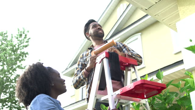 couple doing some home repairs outside house - aggiustare video stock e b–roll