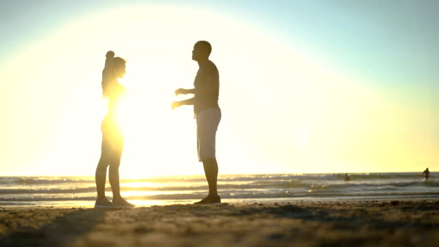 Couple doing stretching exercises at beach
