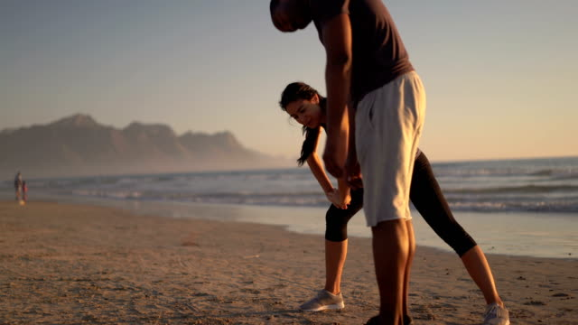 Couple doing stretching exercises on shore