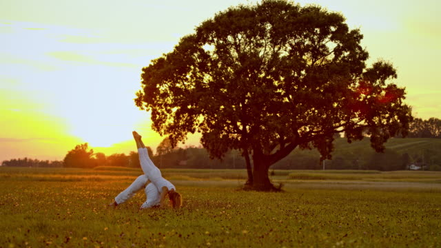 WS Couple doing yoga in grass at sunset